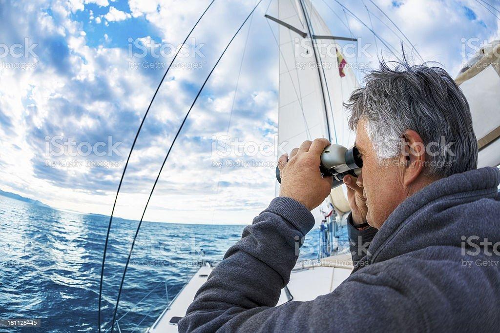 Man on yacht  looks through binoculars stock photo