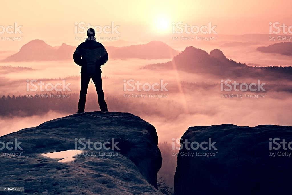 Man onf sandstone rock  watching to Sun. Beautiful moment stock photo
