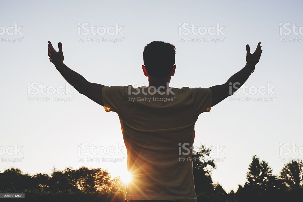 Man open arms at sunrise stock photo