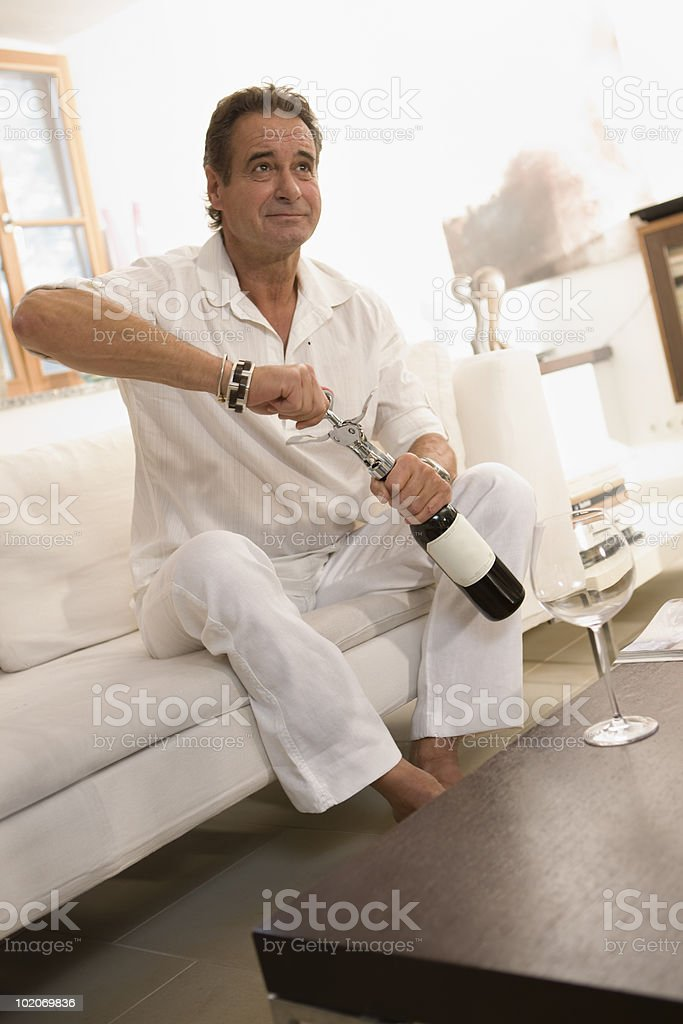 Man opening a bottle of red whine royalty-free stock photo