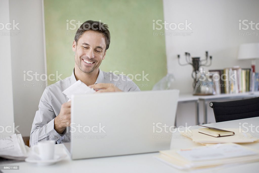 Man opening mail at desk stock photo