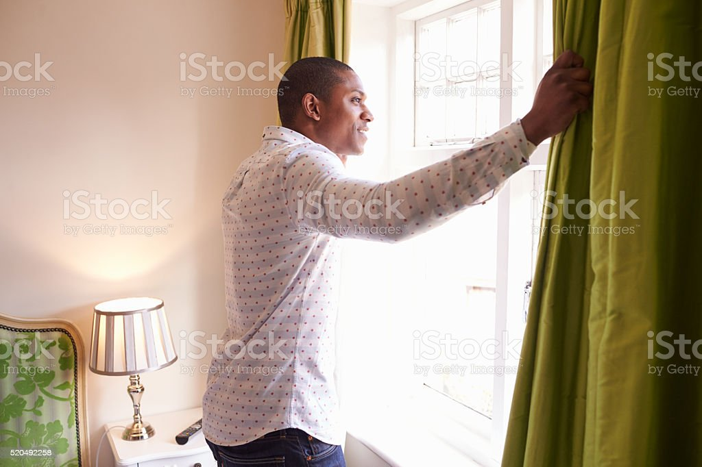 Man opens curtains to look at the view from a hotel stock photo