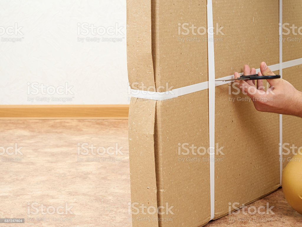 Man  opens the box with furniture. stock photo