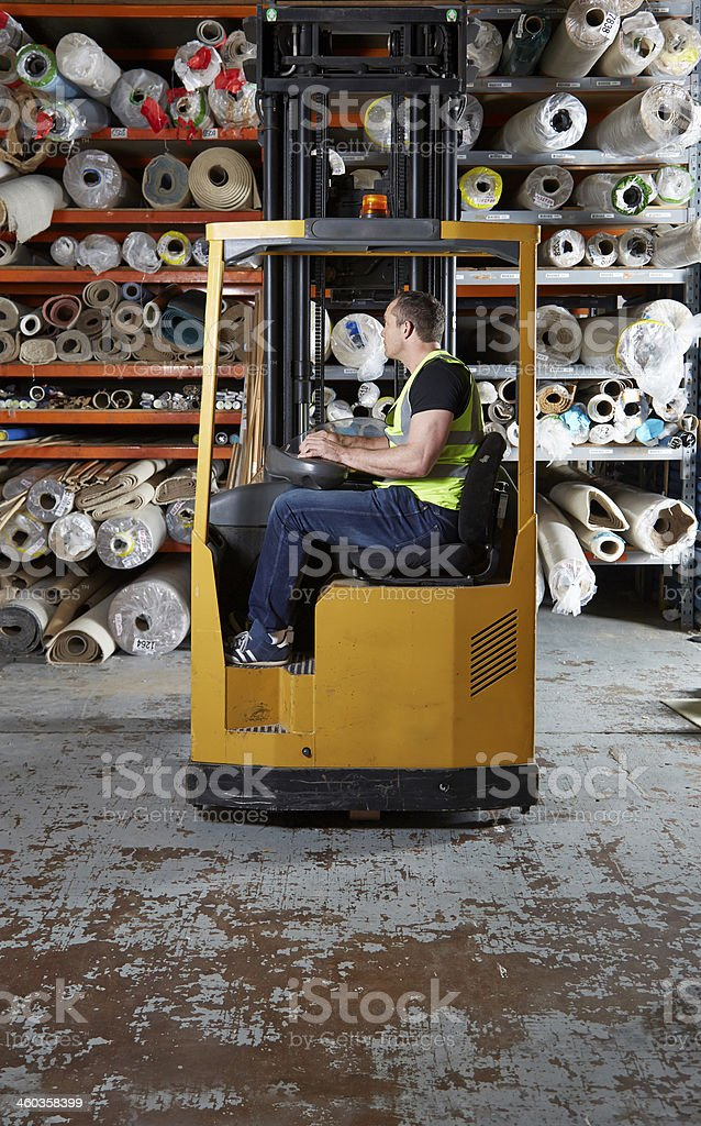 Man operating a forklift truck in warehouse stock photo