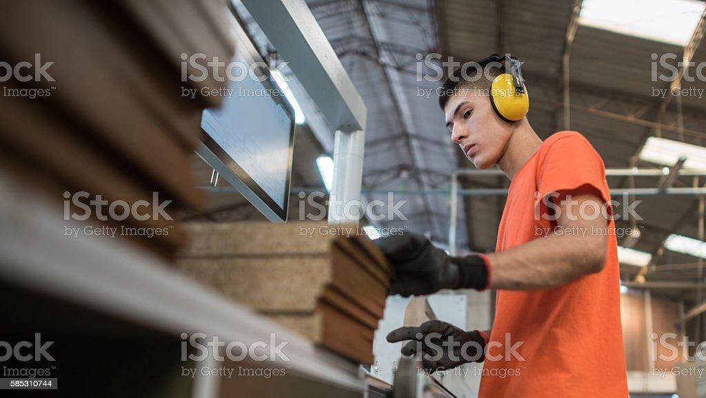 Man operating a machine at a lumberyard stock photo