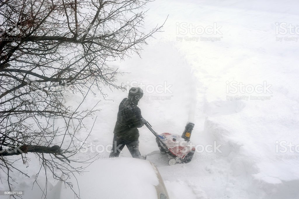 Man Operating a Snow Blower stock photo