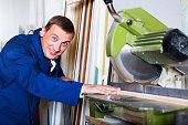 Man operating circular saw in wood workshop