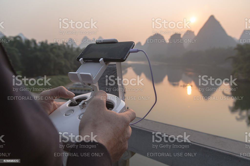 Man operating drone with blue sky background stock photo