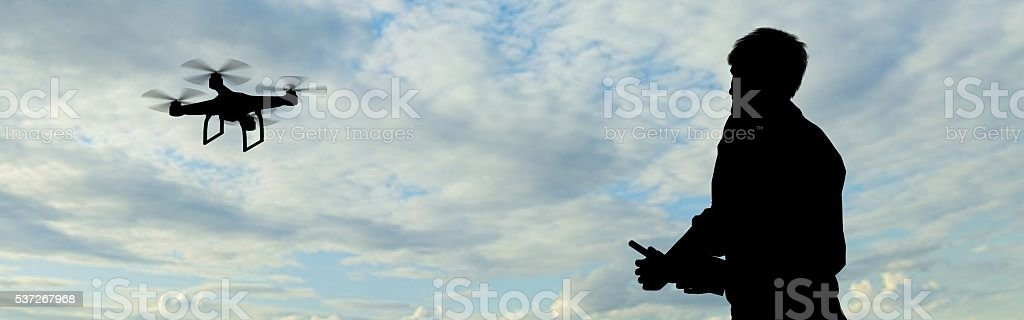 man operating of flying drone quadrocopter at the sky stock photo