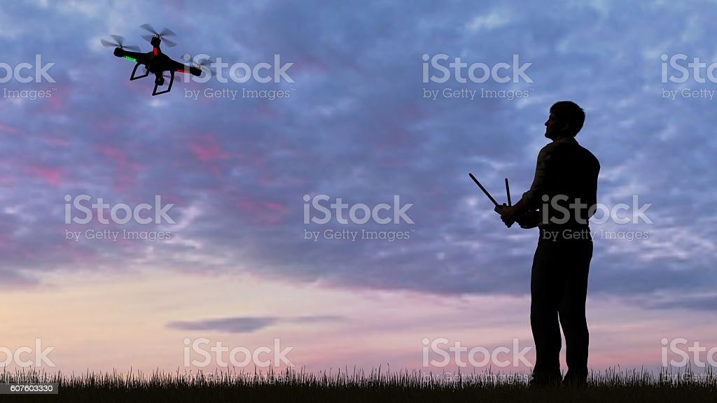 man operating of flying drone quadrocopter UAV at sunset stock photo