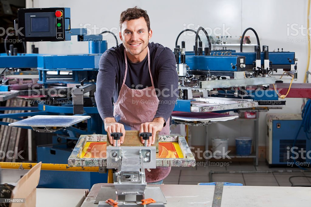 Man operating screen printing equipment stock photo