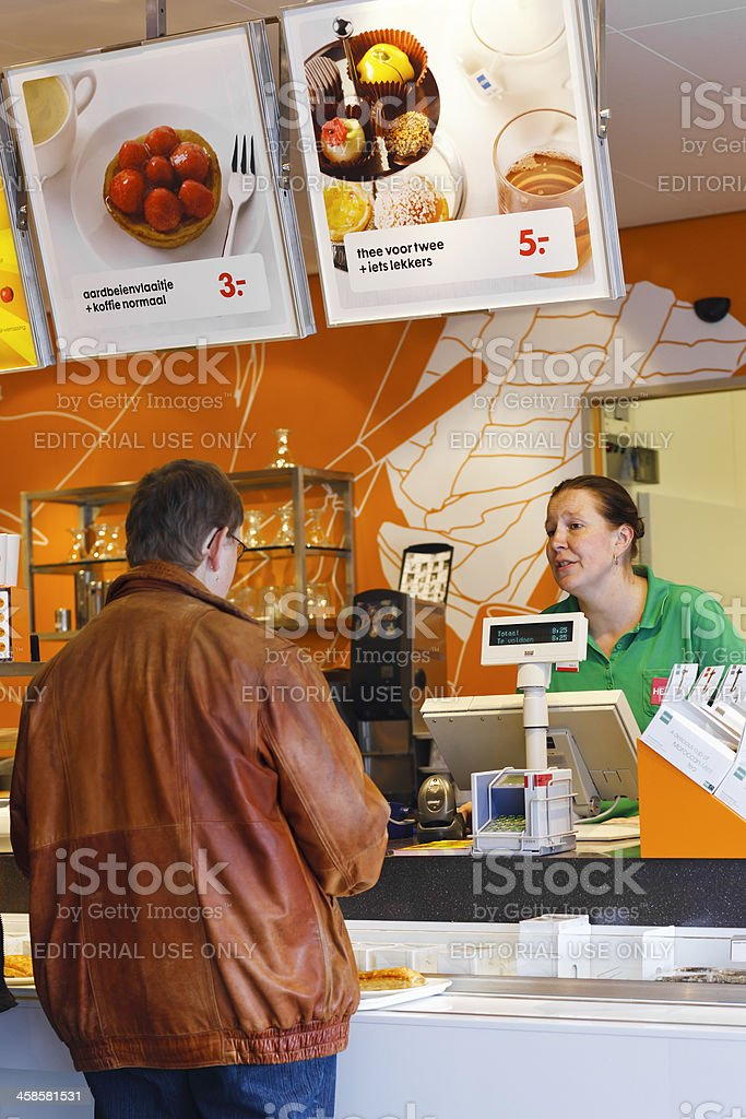 Man ordering coffee at counter in Dutch Hema department store royalty-free stock photo