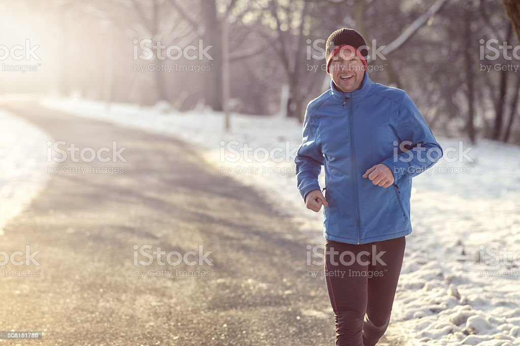 Man out in winter weather for his daily run stock photo