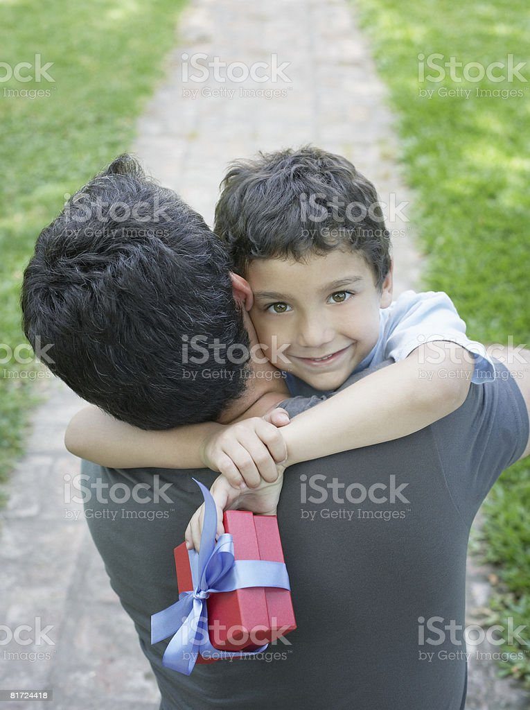 Man outdoors embracing young boy holding gift and smiling royalty-free stock photo