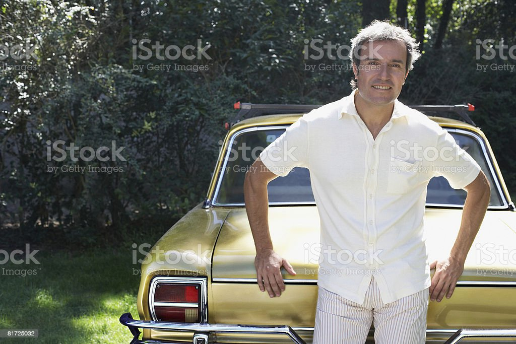 Man outdoors leaning on car smiling royalty-free stock photo