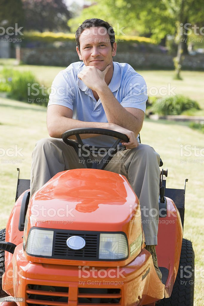Man outdoors on lawnmower smiling stock photo