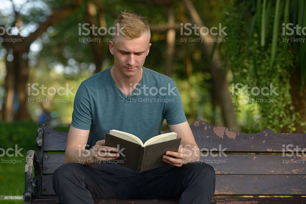 Man outdoors reading book stock photo