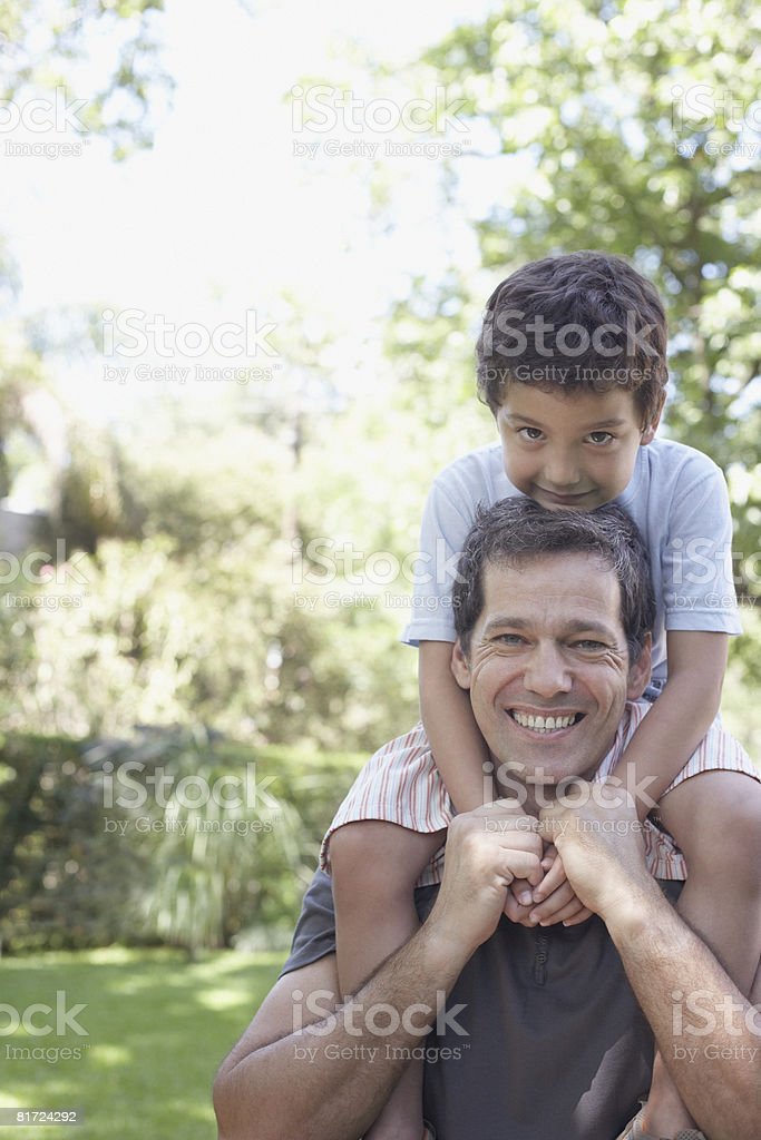 Man outdoors smiling with young boy on shoulders royalty-free stock photo