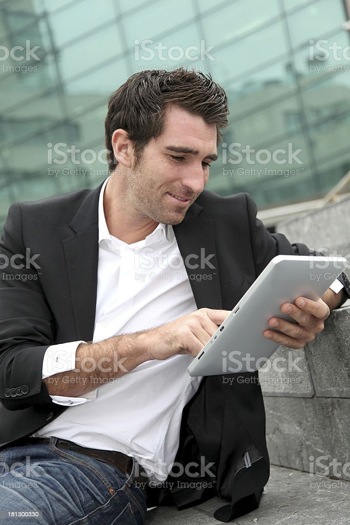 Man outdoors websurfing with tablet in hands royalty-free stock photo
