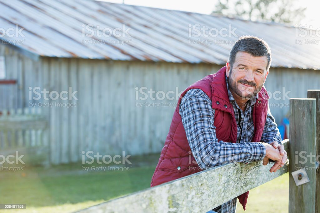 Man outside barn leaning on wooden fence stock photo