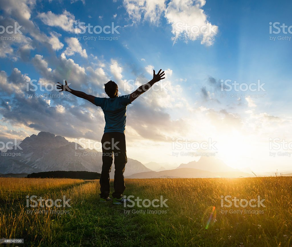 Man outstretching his arms on a sunlit meadow at sunset stock photo