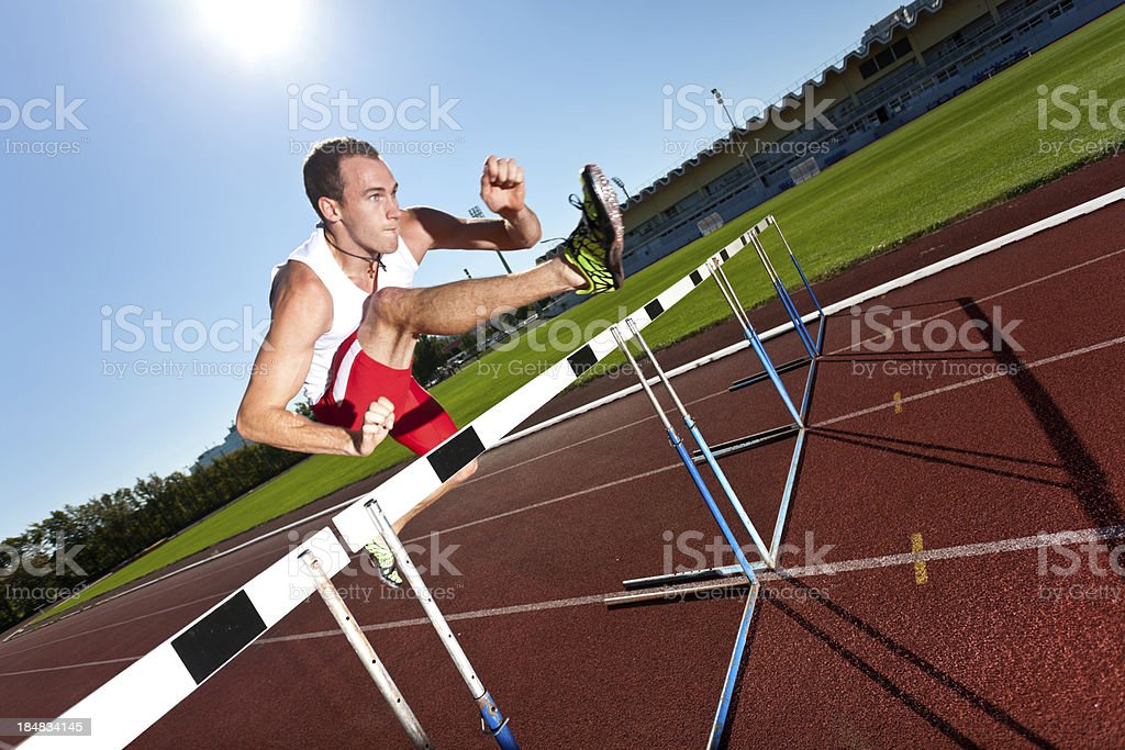 man over hurdle on track stock photo