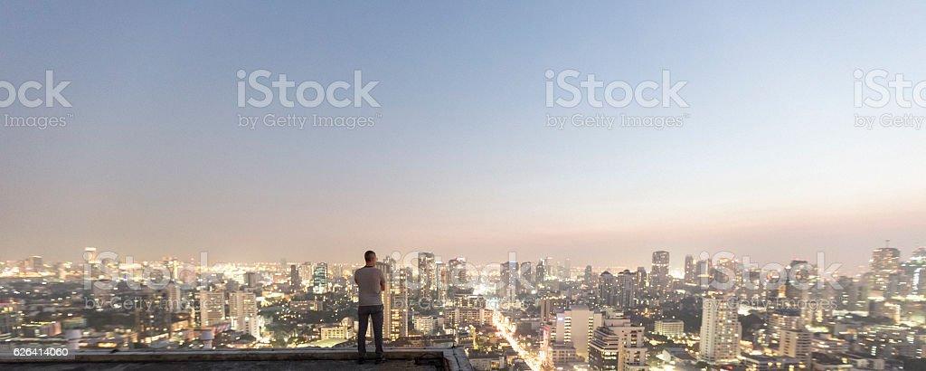 Man over top skyscraper stock photo
