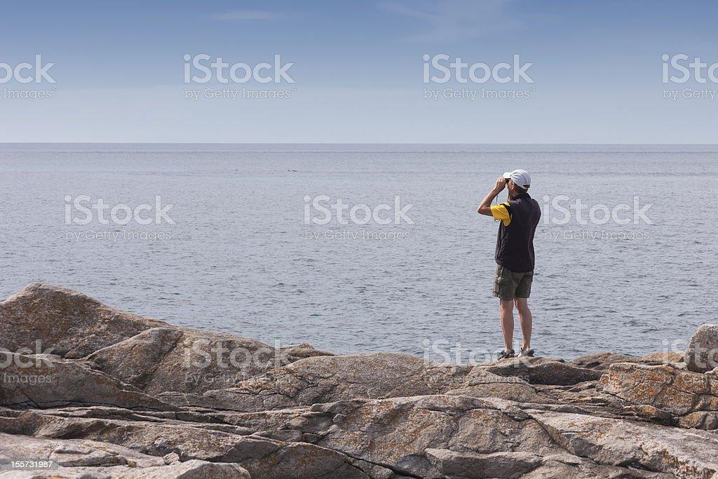 Man overlooking sea with binoculars royalty-free stock photo
