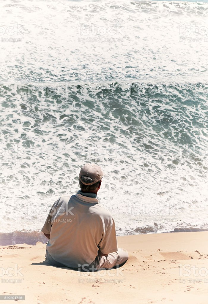 Man overlooking the ocean in Sandwich Harbour,Namibia stock photo