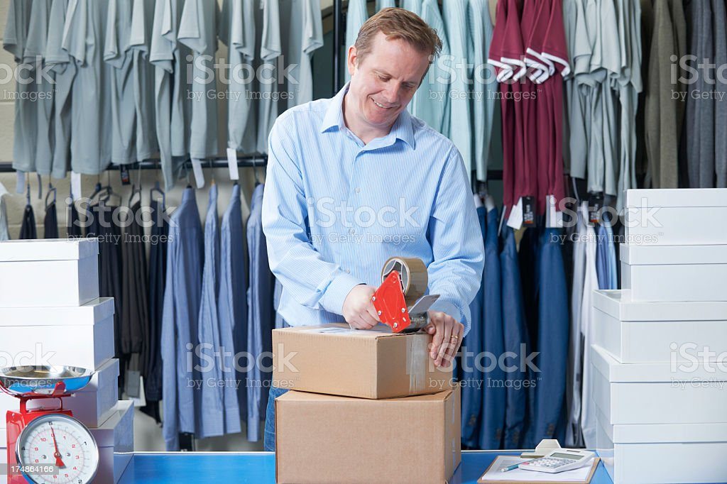 Man packaging clothing for an online store royalty-free stock photo