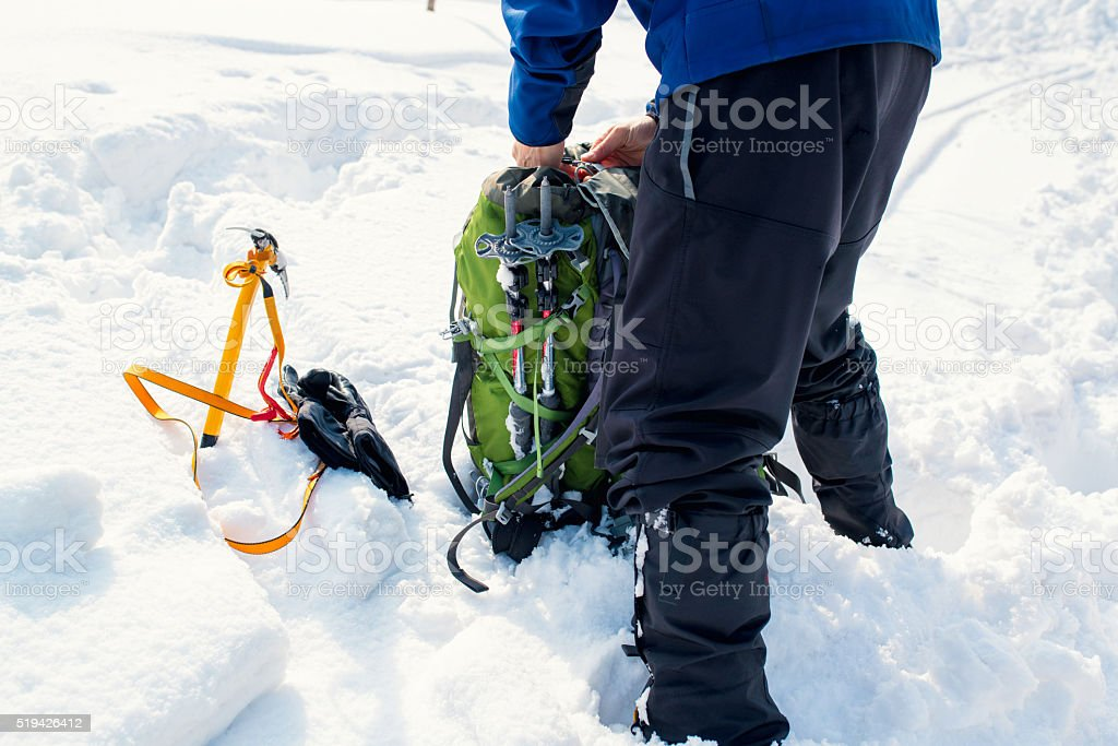 Man packing a bag outside in the snow stock photo