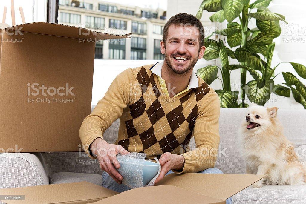 Man Packing or Unpacking at home.  Pomeranian Helping royalty-free stock photo
