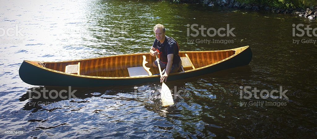 Man Paddling a Classic Vintage Wood and Canvas Canoe. royalty-free stock photo