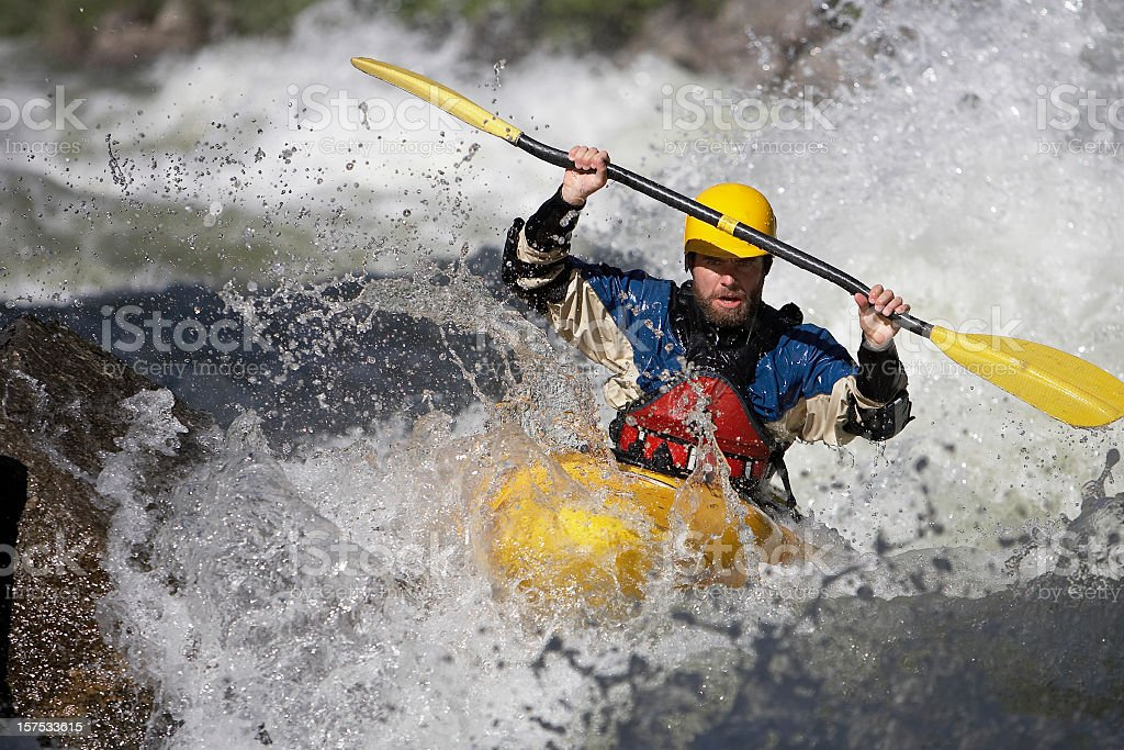 Man Paddling a White Water Kayak on a Idaho River. stock photo