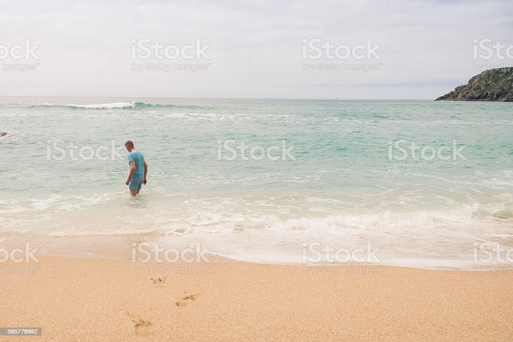 Man paddling at Pedn Vounder Beach, Cornwall. stock photo