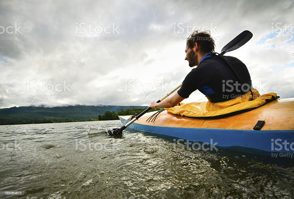 Man paddling in wooden kayak stock photo