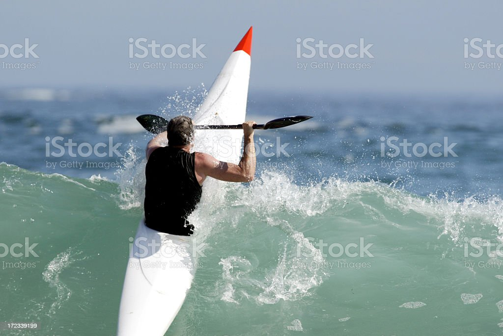 Man paddling over wave in white and red sea kayak royalty-free stock photo