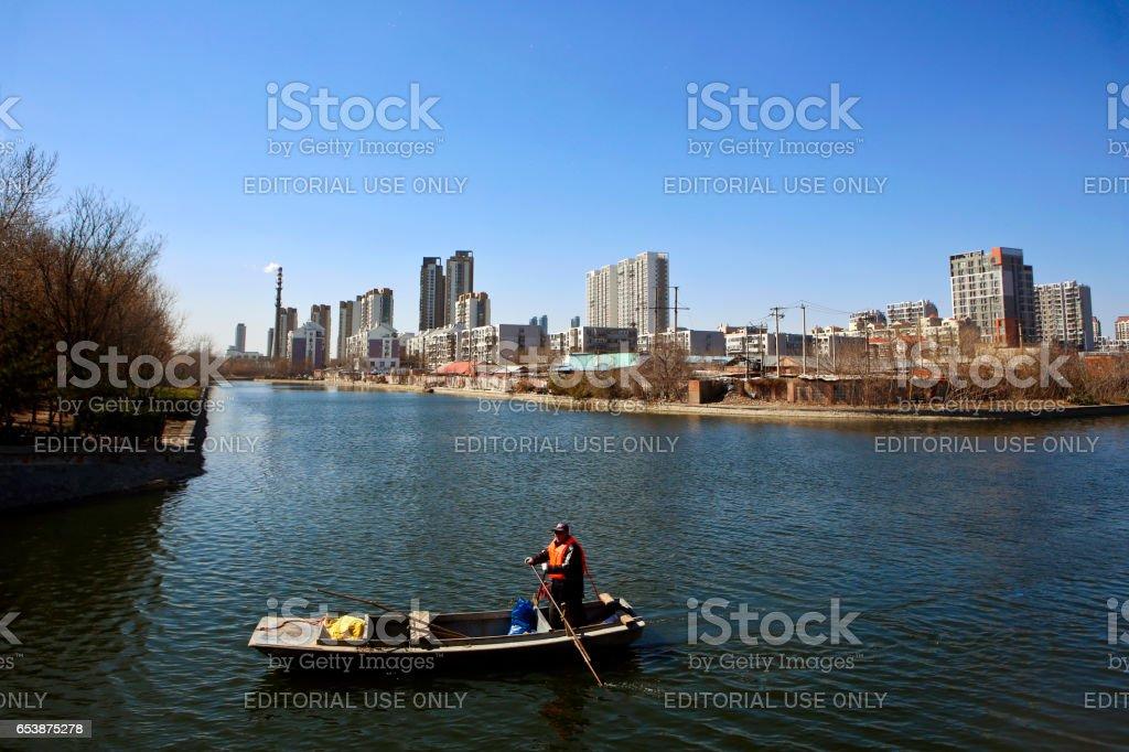Man Paddling Sampan in Canal stock photo