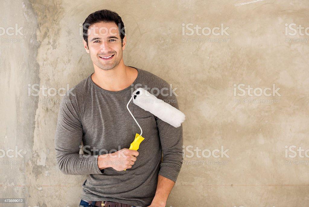 Man painting a wall at home stock photo