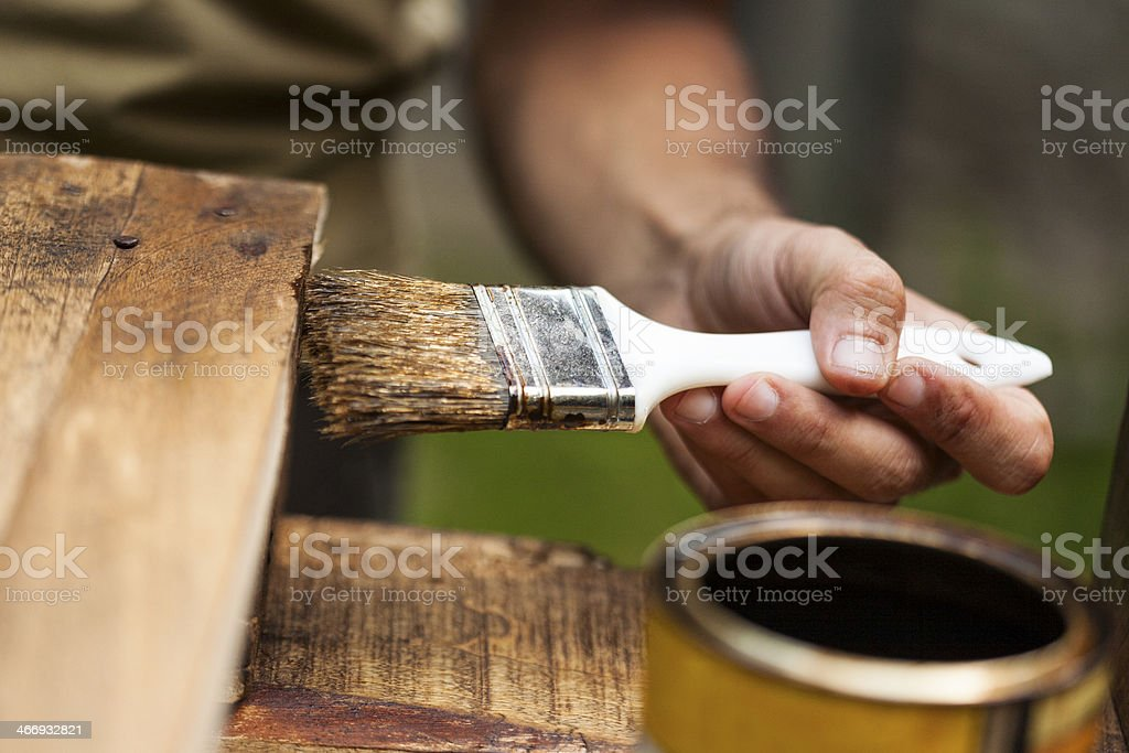 Man painting a wooden deck outdoors stock photo
