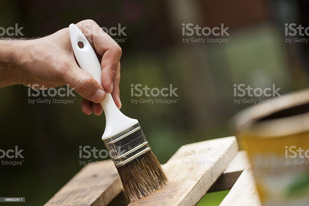 Man painting a wooden deck royalty-free stock photo