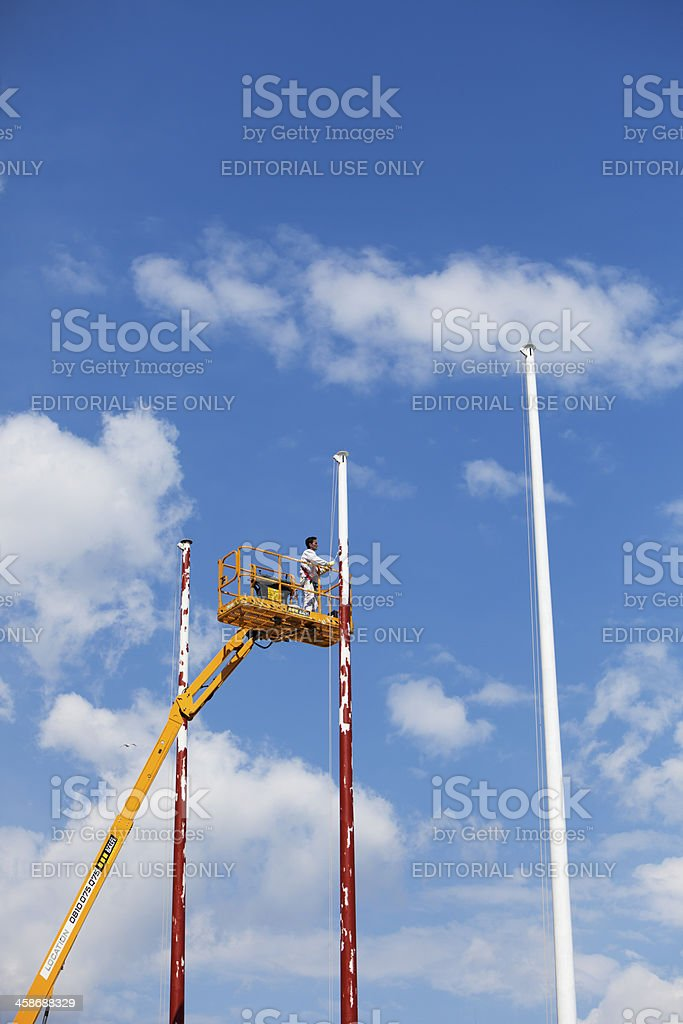 Man painting flagpoles from platform royalty-free stock photo