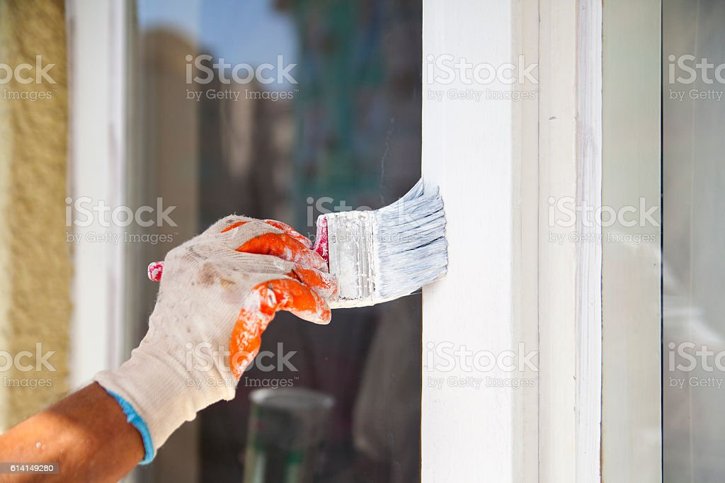 Man painting frame of the window stock photo