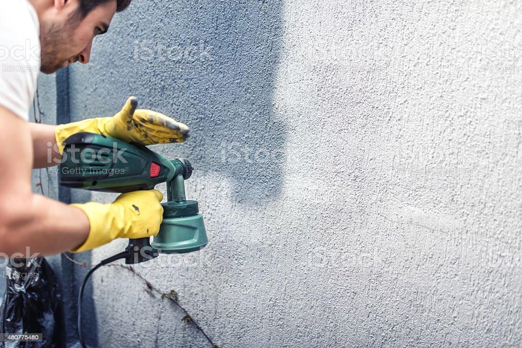 Man painting grey wall, renovating exterior walls of new house stock photo
