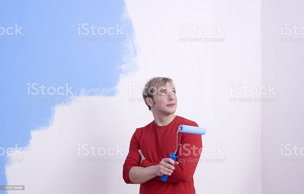 Man painting room with roller stock photo