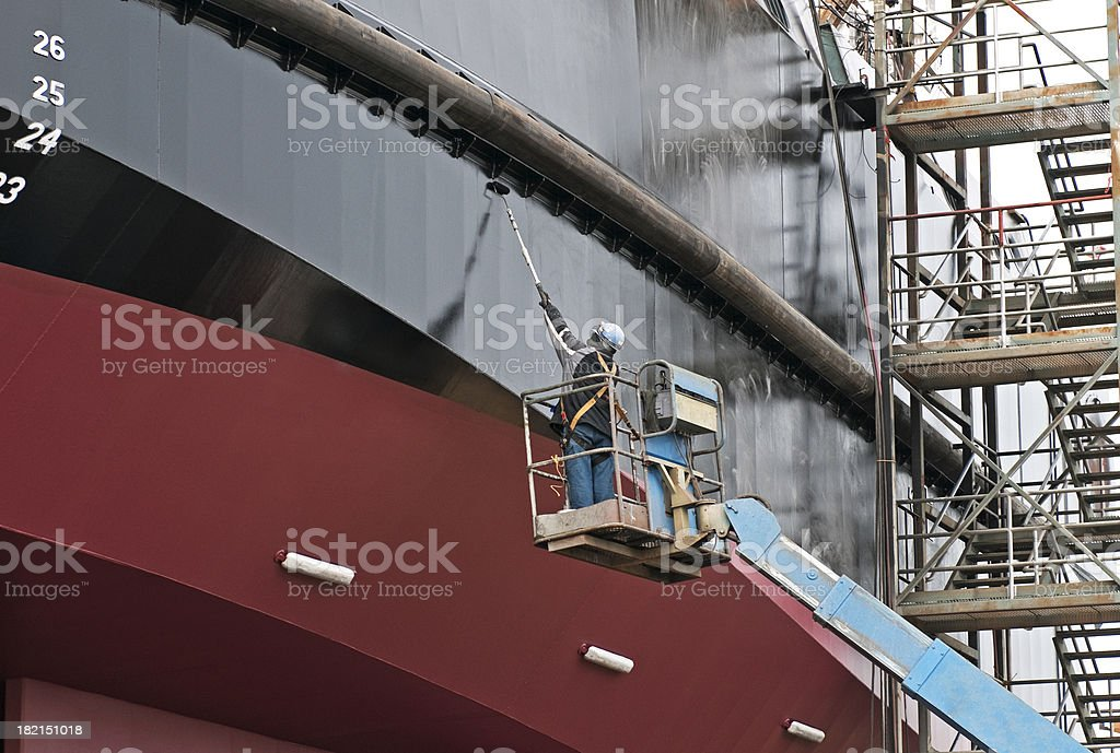Man painting ship in dry dock stock photo
