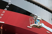 Man painting ship's hull with roller