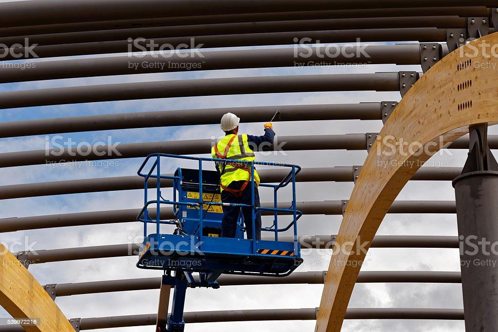 man painting steelwork stock photo