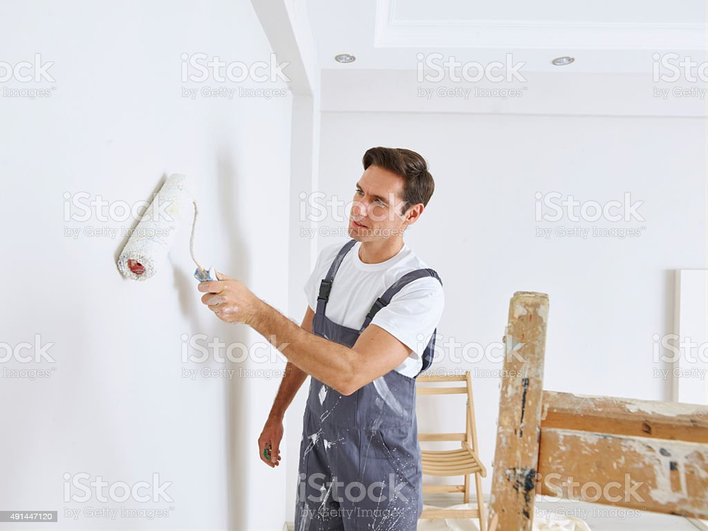 Man painting wall with a roller stock photo