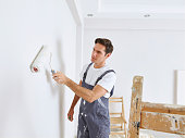 Man painting wall with a roller
